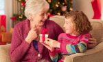 Внучка дарит подарок бабушке под новогодней елочкой